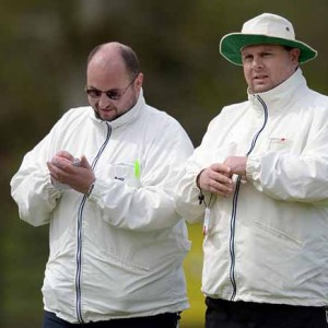 Steve Wood, left, makes a note of the scoring while his fellow-umpire, William Clarke, keeps an eye on the field of play.
